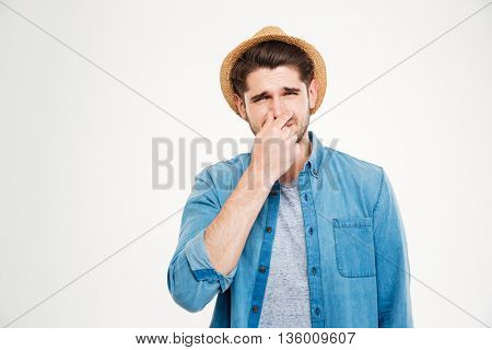 Upset young man covered his nose by hand and feeling bad smell over white background