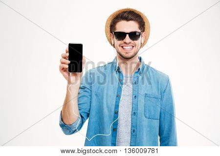 Happy handsome young man listening to music and showing blank screen mobile phone over white background