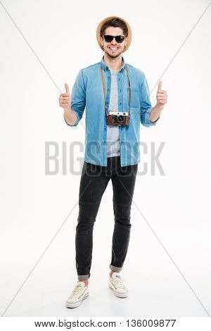 Full length of happy confident young man with old vintage camera showing thumbs up over white background