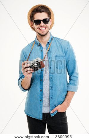 Cheerful young man in sunglasses and hat using old vintage photo camera over white background