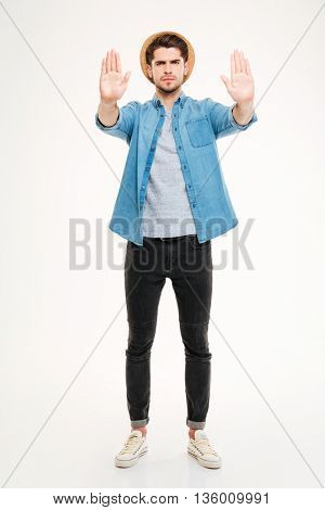 Full length of angry young man standing and showing stop gesture over white background