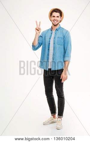 Full length of smiling young man standing and showing peace sign over white background