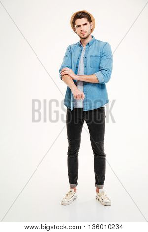 Full length of angry young man rolling up his sleeves over white background