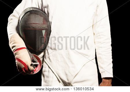 Mid-section of man standing with fencing mask on black background