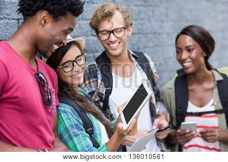 Happy woman showing digital tablet to her friends