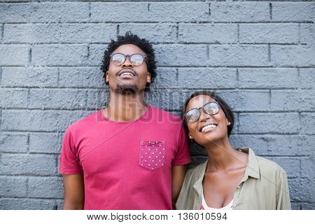 Young couple in spectacles leaning against wall
