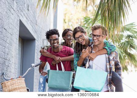 Young men giving piggyback to women having fun