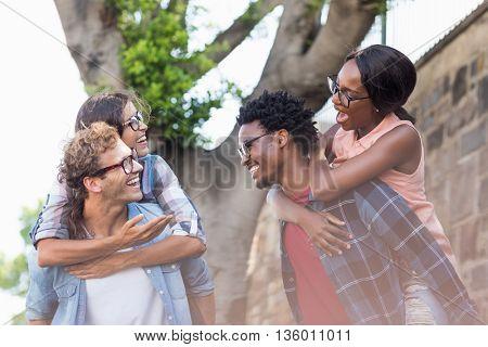 Young men giving piggyback to women outdoors