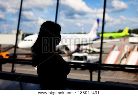 Silhouette of woman looking through window in the airport