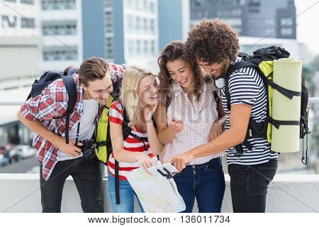 Group of friends looking in mobile phone on terrace