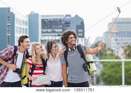 Group of friends taking selfie with selfie stick on terrace