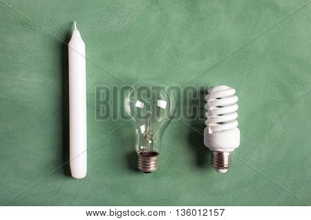 White candle and electric bulbs on the green chalkboard. Concept describing the evolution of lighting