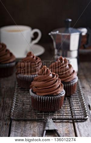 Chocolate cupcakes with coffee and whipped ganache on a cooling rack