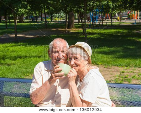 The happy old couple drinking tea in the summer on a walk in park