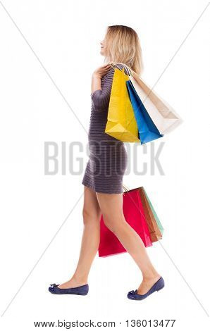 back view of going  woman  with shopping bags. beautiful girl in motion.  backside view of person. Rear view people collection. Isolated over white. Girl in dress is right throwing shoulder paper bags