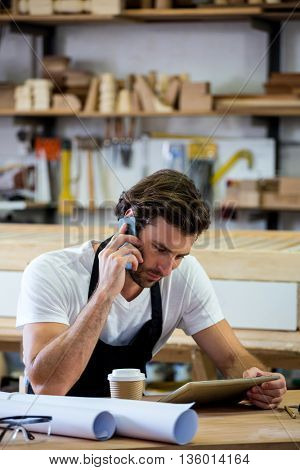 Carpenter calling someone and looking at his tablet in a dusty workshop