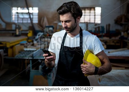 carpenter texting someone and holding his helmet in a dusty workshop