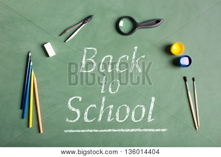 Back to school concept. Compass magnifying glass brush eraser on the black chalkboard.