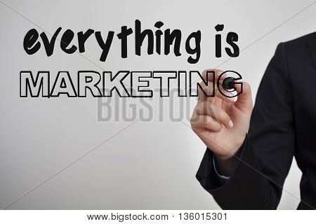 Everything is Marketing word written by man hand holding  pen
