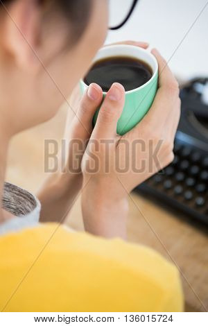 Hipster holding a cup of coffee in the office