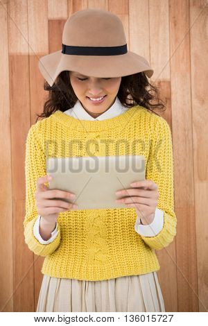Hipster using a tablet on wooden background