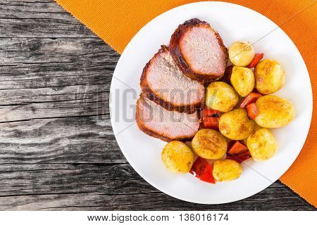 Oven Baked new potatoes with sea salt red bell pepper and pork tenderloin cutting into pieces in aplate on a table mat on a wooden table close-up view from above
