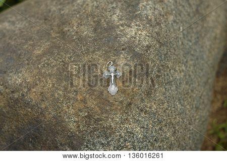 orthodox silver cross on big stone close up