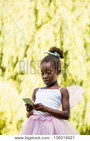 Cute mixed-race girl wearing a fairy dress and using a smartphone on a park