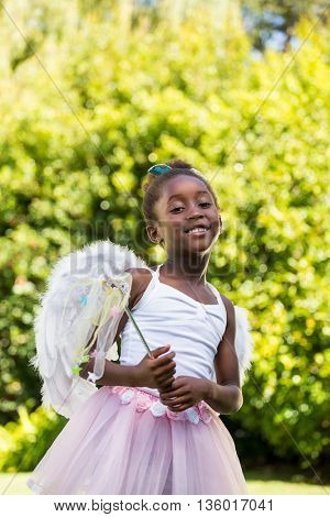 Cute mixed-race girl smiling and posing with a fairy dress on a park