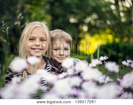 Summer. Beautiful blond girl and adorable boy hiding in flowers