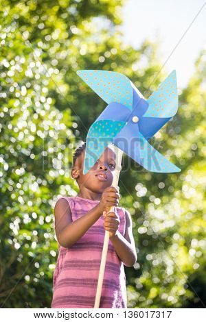 Boy playing with a pinwheel in a park