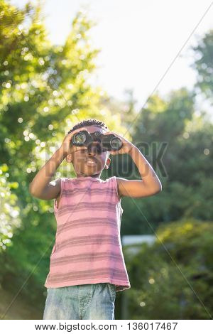 Boy looking through binoculars in a park