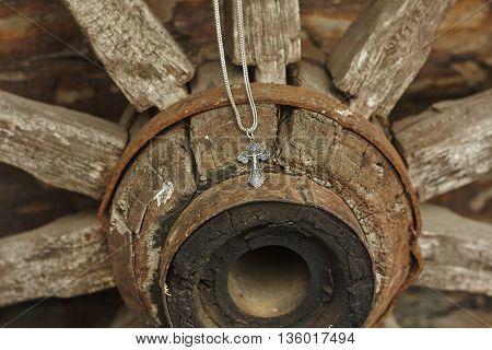 orthodox silver cross on chain on vintage wheel