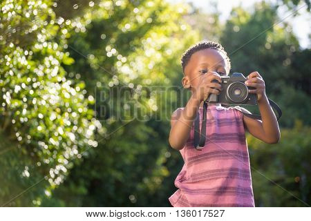 Child is using a camera in a park