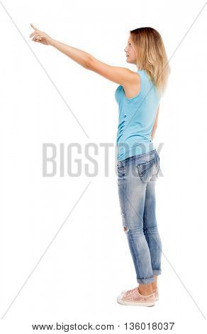 Back view pointing woman. beautiful girl. Rear view people collection.  backside view person.  Isolated over white background. girl in jeans and a blue t-shirt standing sideways and shows a hand up.