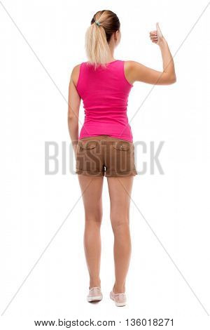 Back view of  woman thumbs up. Rear view people collection. backside view of person. Isolated over white background. Blonde in brown shorts showing a thumbs up with his left hand.