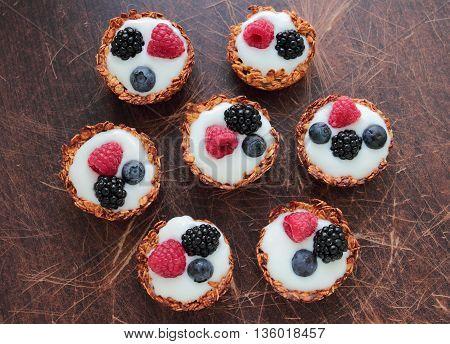 Homemade oatmeal tarts with light yogurt and fresh blackberries raspberries and bilberries