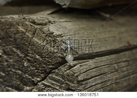 orthodox silver cross on old lumber wall