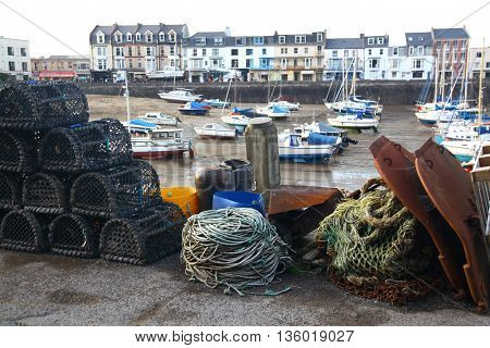 Lobster pots and other fishing equipment stacked on the quay at Ilfracombe awaiting loading the next fishing boat.