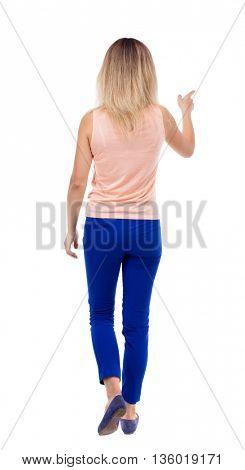 back view of walking  woman. beautiful girl pointing.  backside view of person.  Rear view people collection. Isolated over white background. The blonde in a pink jacket goes forward pointing to left.