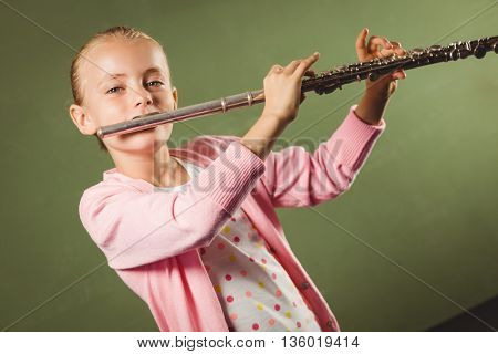 Girl playing the flute on green background