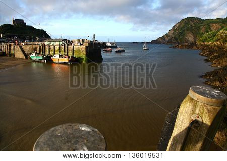 Last rays of sunshine strike the quay at Ilfracombe as the tide turns