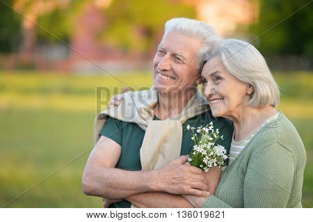 Loving mature couple  in summer park with flowers