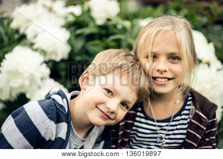 Summer. Beautiful blond girl and adorable boy looking at the camera and smiling.