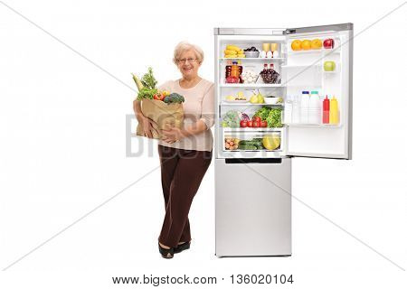 Senior lady holding a grocery bag and leaning on an open refrigerator isolated on white background
