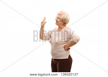 Elderly woman waving to someone with her hand isolated on white background