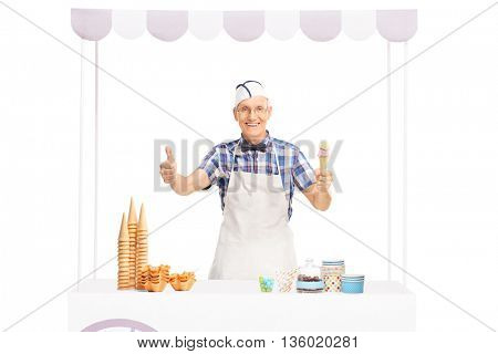 Elderly ice cream vendor standing behind a stall and giving a thumb up isolated on white background