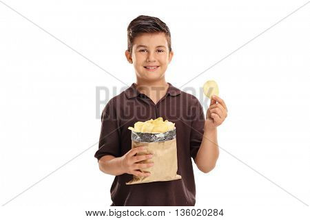 Little kid holding a bag of potato chips in on e hand and a single chip in the other isolated on white background