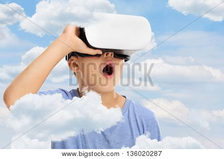 Amazed kid looking in virtual reality goggles and feeling like he is in clouds