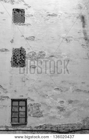 the old big plastered brick wall with windows for ancient background of monochrome tone